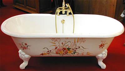 чугунная ванная с фигурными ножками и рисунком сбоку на эмали